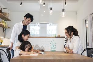 勉強をする姉妹と見守る両親の写真素材 [FYI04611762]