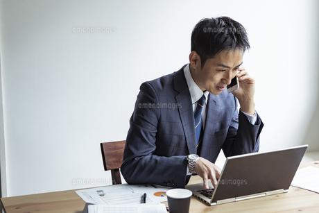 ノートパソコンを見ながらスマートフォンで話すビジネスマンの写真素材 [FYI04611991]