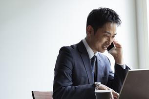 ノートパソコンを見ながらスマートフォンで話すビジネスマンの写真素材 [FYI04611995]