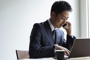 ノートパソコンを見ながらスマートフォンで話すビジネスマンの写真素材 [FYI04611996]