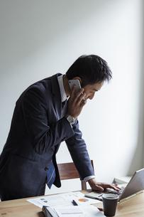 ノートパソコンを見ながらスマートフォンで話すビジネスマンの写真素材 [FYI04612001]