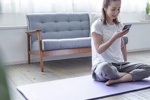スマートフォンで音楽を聴く日本人女性の写真素材 [FYI04612099]