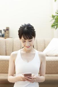 ソファーの前でスマートフォンを操作する女性の写真素材 [FYI04612158]