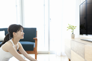 テレビの前に座る女性の写真素材 [FYI04612180]