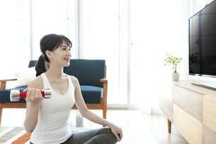 テレビの前に座る女性の写真素材 [FYI04612181]