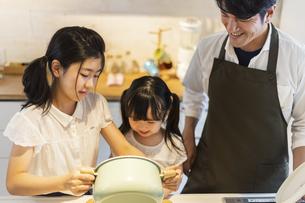 キッチンに立つ家族の写真素材 [FYI04613089]