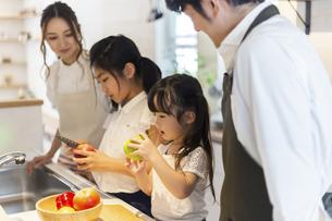 キッチンに立つ家族の写真素材 [FYI04613092]