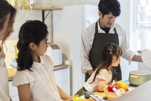 キッチンに立つ家族の写真素材 [FYI04613098]