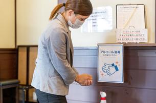 マスクをした働く女性が感染予防の為に手首消毒をアルコールやエタノールや消毒ジェルで消毒するの写真素材 [FYI04613146]
