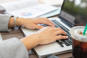 ノートパソコンでタイピングをする女性の写真素材 [FYI04613160]