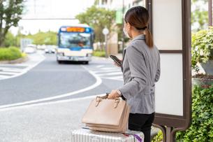 バス停でスーツケースを持ってバスを待つ女性の写真素材 [FYI04613164]