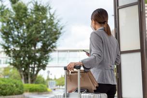 バス停でスーツケースを持ってバスを待つ女性の写真素材 [FYI04613165]