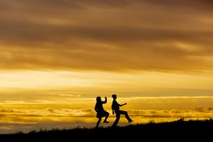 夕陽を背景に元気よく歩く若い男女のシルエットの写真素材 [FYI04613170]