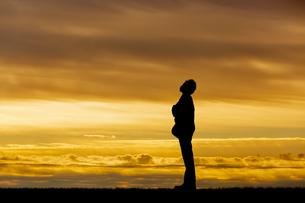 夕陽を背景に腕組みし立つ男性の横姿シルエットの写真素材 [FYI04613187]