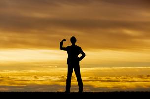 夕陽を背景にガッツポーズをする男性のシルエットの写真素材 [FYI04613188]