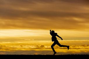 夕陽を背景に元気よく走る男性のシルエットの写真素材 [FYI04613189]