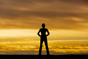 夕陽を背景に腰に手を当て立ち姿の男性のシルエットの写真素材 [FYI04613192]