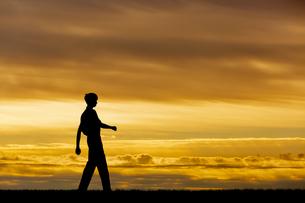 夕陽を背景に元気よく歩く男性のシルエットの写真素材 [FYI04613198]