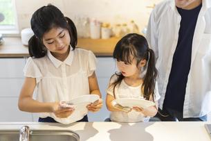 お皿を拭く姉妹の写真素材 [FYI04613227]