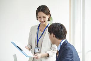パソコンを開き仕事をするビジネスマンとビジネスウーマンの写真素材 [FYI04613333]