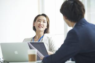 パソコンを開き仕事をするビジネスマンとビジネスウーマンの写真素材 [FYI04613343]
