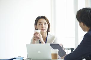 パソコンを開き仕事をするビジネスマンとビジネスウーマンの写真素材 [FYI04613346]