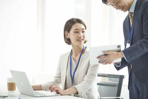 パソコンを開き仕事をするビジネスマンとビジネスウーマンの写真素材 [FYI04613347]