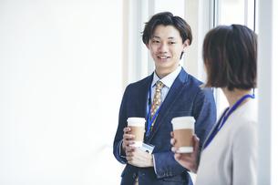 立ち話をするビジネスマンとビジネスウーマンの写真素材 [FYI04613348]