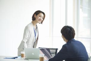 パソコンを開き仕事をするビジネスマンとビジネスウーマンの写真素材 [FYI04613349]