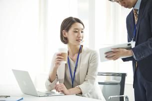 パソコンを開き仕事をするビジネスマンとビジネスウーマンの写真素材 [FYI04613350]
