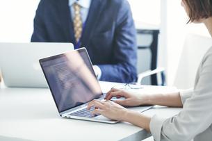 パソコンを開き仕事をするビジネスマンとビジネスウーマンの写真素材 [FYI04613361]