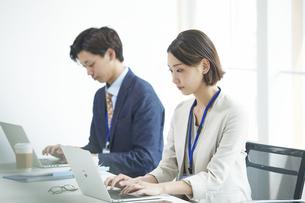 パソコンを開き仕事をするビジネスマンとビジネスウーマンの写真素材 [FYI04613370]