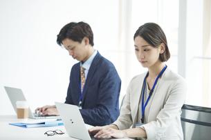 パソコンを開き仕事をするビジネスマンとビジネスウーマンの写真素材 [FYI04613371]