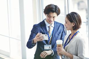 スマートフォンを見るビジネスマンとビジネスウーマンの写真素材 [FYI04613373]