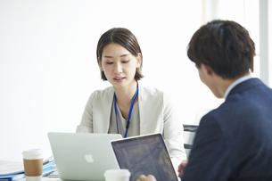 パソコンを開き仕事をするビジネスマンとビジネスウーマンの写真素材 [FYI04613376]