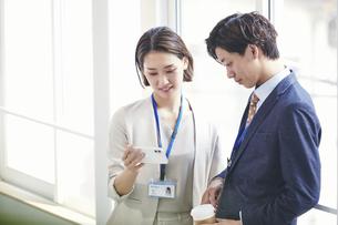 スマートフォンを見るビジネスマンとビジネスウーマンの写真素材 [FYI04613378]