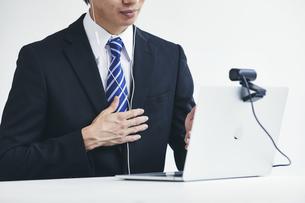 カメラに向かって話すスーツを着た若い男性とパソコンの写真素材 [FYI04613637]