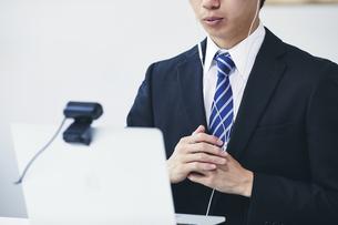 カメラに向かって話すスーツを着た若い男性とパソコンの写真素材 [FYI04613644]