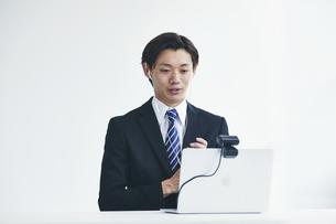 カメラに向かって話すスーツを着た若い男性とパソコンの写真素材 [FYI04613648]
