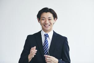 カメラに向かって話すスーツを着た若い男性の写真素材 [FYI04613666]