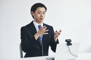 カメラに向かって話すスーツを着た若い男性とパソコンの写真素材 [FYI04613684]