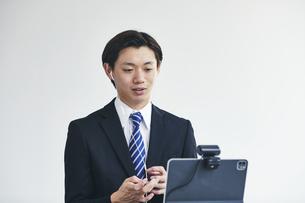 カメラに向かって話すスーツを着た若い男性とタブレット端末の写真素材 [FYI04613686]