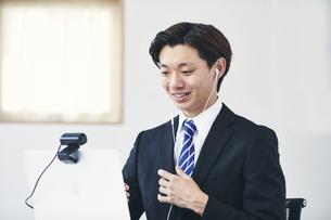 カメラに向かって話すスーツを着た若い男性とパソコンの写真素材 [FYI04613730]