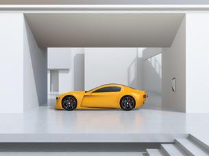 自宅充電スタンドに充電している黄色電動スポーツカーのイメージの写真素材 [FYI04614424]
