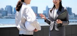 打ち合わせする女性作業員とビジネスウーマンの写真素材 [FYI04615043]