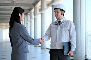 握手する男性作業員とビジネスウーマンの写真素材 [FYI04615130]