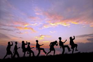 夕陽を背景に元気よく歩く多数の若い男女のシルエットの写真素材 [FYI04616682]