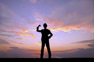 夕陽を背景にガッツポーズをする若い男性のシルエットの写真素材 [FYI04616702]