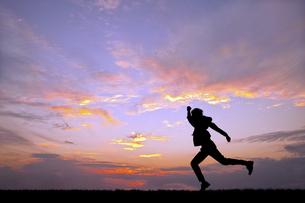 夕陽を背景に元気よく走る男性のシルエットの写真素材 [FYI04616703]
