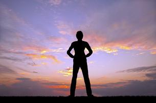 夕陽を背景に腰に手を当て立ち姿の若い男性のシルエットの写真素材 [FYI04616706]